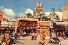 Många personer som går på gatan med marknaden och den hinduiska templet Arkivfoto
