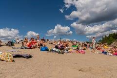 Många personer som solbadar och har picknicken på en strand med blå himmel och moln Arkivfoton