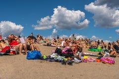 Många personer som solbadar och har picknicken på en strand med blå himmel och moln Arkivbilder