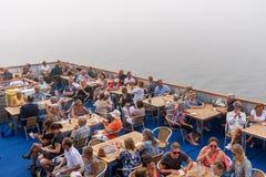 Många personer som utomhus sitter på däck på på kryssningskeppet Royaltyfri Fotografi