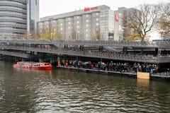 Många personer som väntar i linje vid vattnet på ett läge för uppsamling för kryssning för kanalfartyg arkivfoton