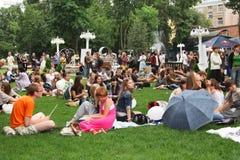 Många personer vilar i parkera på gräsmattorna moscow 01 08 Arkivbilder