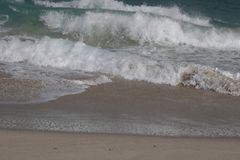 Många plaska vågor som rusar till sanden royaltyfri foto