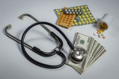 Många preventivpillerar, en stetoskop och pengar på en tabell Arkivfoton