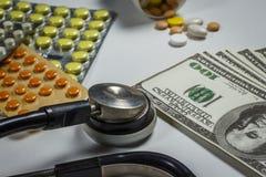 Många preventivpillerar, en stetoskop och pengar på en tabell Royaltyfri Bild