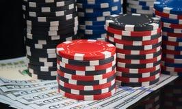Många pyramider av kulöra chiper, för att spela i kasinot, på den svarta tabellen och dollarna, närbild fotografering för bildbyråer
