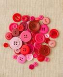 Högen av rött och rosa färg knäppas på hessian arkivfoto