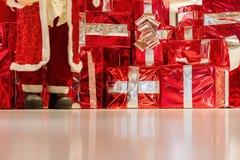 Många röda gåvaaskar med guld- band- och för jultomten` s fot på skinande bakgrund Jul bakgrund, gåvor som shoping Fotografering för Bildbyråer