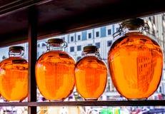 Många runda flaskor för olika format med den röda genomskinliga vätskeställningen på shalved trä mot stort fönster med gatan in Arkivbilder