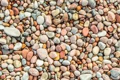 Många rundar och slätar färgrika kiselstenar som ses från över Arkivfoton