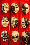 Många särskiljande Venetian karnevalmaskeringar av olika färger, röd bakgrund Arkivbilder