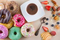 Många söta donuts med koppen av aromkaffe, frukter och en biten rosa munk på ljus stenbakgrund arkivbild