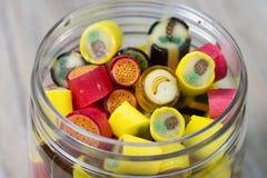 Många söta färgrika godisar i öppnad glass krus Arkivfoton
