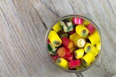 Många söta färgrika godisar i öppnad glass krus på träbakgrund Royaltyfria Bilder
