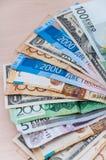 Många sedlar av olika länder av världen, skillnaden i värde som staplas på tabellen med en fan royaltyfri fotografi