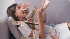 Många sedlar flyger i luftfasta utgiften i ultrarapid En flicka ligger och mycket pengarnedgångar på henne den lyckliga kvinnan j arkivfilmer
