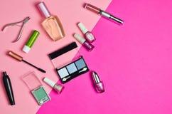 Många skönhetsmedel anmärker för att applicera makeup på en rosa bakgrund What& x27; s i women&en x27; kosmetisk påse för s? Arkivbilder