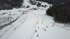 Många skidåkare och snowboarders stiger ned ner skidalutningen stock video