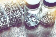 Många skruvar, muttrar - och - bultar i flaskan för hem- bruk arkivbilder