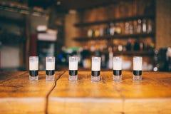 Många små alkoholiserade coctailar b 52 på trästången Royaltyfri Fotografi