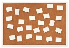 Många små ark av papper på informationskork stiger ombord arkivbilder