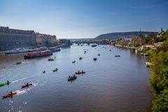 Många små fartyg och kanoter med folk som paddlar på floden i centrala Prague royaltyfri foto