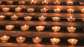 Många små kyrkliga stearinljus bränner på altaret
