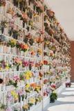 Många små nischer av en kyrkogård med plast- blommor royaltyfria foton