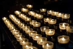 Många små stearinljus i den kyrkliga blixten i mörkret arkivbild