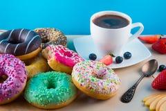 Många smakliga donuts med koppen av aromkaffe, frukter och en biten rosa munk på ljus stenbakgrund royaltyfria bilder