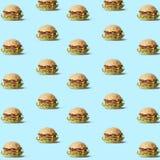 Många smakliga klipska hamburgare på blåtttextur Royaltyfri Bild