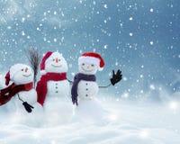 Många snögubbear som står i vinterjullandskap royaltyfria bilder