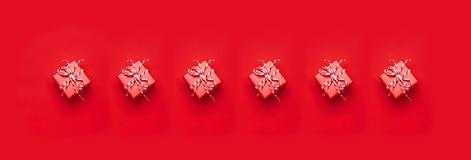 Många snör åt den röda gåvaasken med dekorativt på röd bakgrund som lägenheten för den bästa sikten lägger Semestra gåva för aske arkivfoto