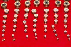 Många sort och format av nolla-cirkel den raka proppskruven för industriellt som i rad sätts på röd bakgrund royaltyfria foton