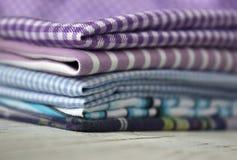 Många sorter av bomullstyger i band och buren på en lila bakgrund arkivfoton