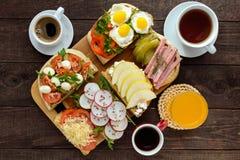 Många sorter av smörgåsar, bruschettaen och te, kaffe, ny fruktsaft - för en familjfrukost Fotografering för Bildbyråer