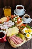 Många sorter av smörgåsar, bruschettaen och te, kaffe, ny fruktsaft - för en familjfrukost Arkivbild