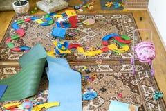 Många spridda leksaker för barn` s i rummet Barn lämnade en röra i rummet Royaltyfri Foto