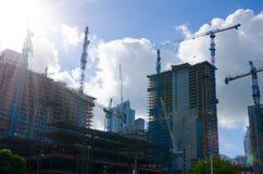 Många stadsbyggnader under kranar för konstruktionsplats Arkivbild