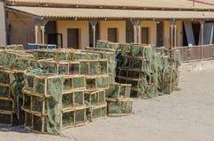Många staplade hummer- eller kräftafällor framme av gammal byggnad, Luderitz, Namibia, sydliga Afrika Royaltyfria Foton