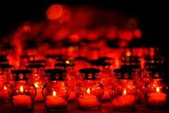 Många stearinljus som bränner i röda stearinljushållare på natten royaltyfri bild