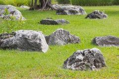 Många stenar vaggar svarta grupper för fältet för objektgårdgräs, naturlandskap somsikten parkerar royaltyfria bilder
