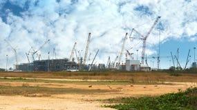 Många sträcker på halsen och byggnadskonstruktionsplatsen mot blå himmel Arkivbild