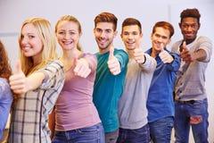 Många studenter som rymmer upp tummar Royaltyfri Foto