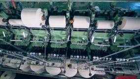 Många sy rullar som roterar på en textilfabriksmaskin stock video