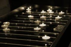 Många tända stearinljus i kyrka Fotografering för Bildbyråer