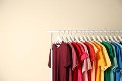 Många t-skjortor som hänger i beställning av regnbågen, färgar arkivfoto