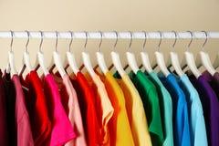 Många t-skjortor som hänger i beställning av regnbågen, färgar arkivbild