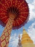 Många-tiered paraply med chedi- eller pagodbakgrund i Wat Phra That Hariphunchai i Lamphun, Thailand Royaltyfri Fotografi