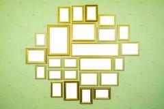 Många tomma guld- träramar med kopieringsutrymme på den gröna väggen royaltyfri fotografi